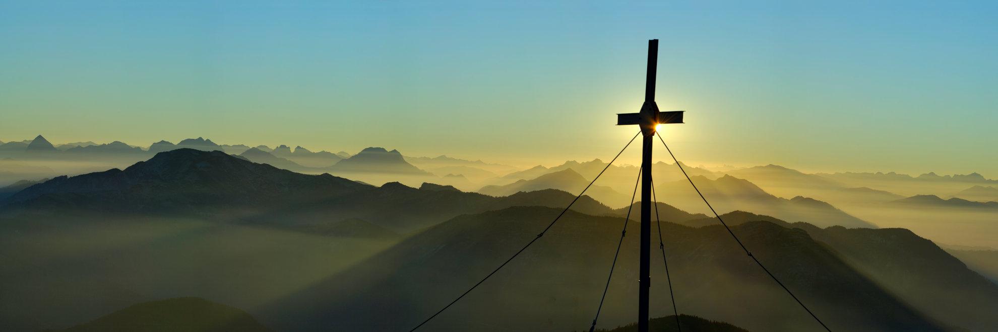 Gipfelkreut bei Sonnenuntergang, Begleitung von Unternehmen um Alltag